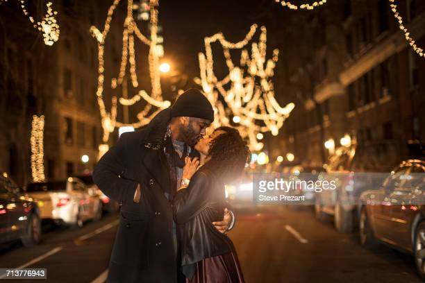 romantic couple kissing by christmas lights at night, new york, usa - black people kissing stock pictures, royalty-free photos & images