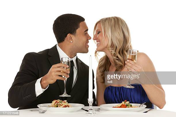 romantic couple kissing each other at a dining table - black women kissing white men stock pictures, royalty-free photos & images