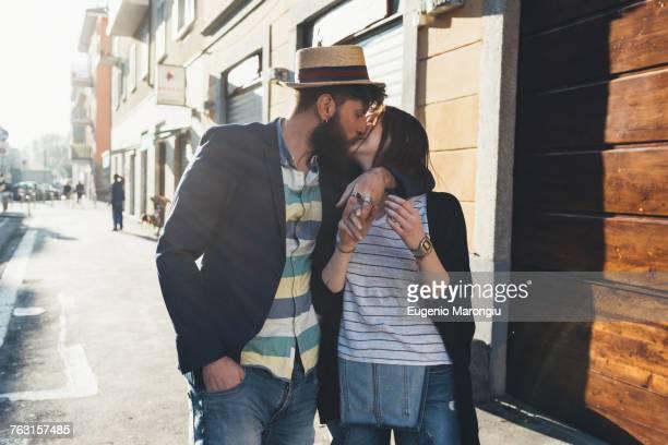 Romantic couple kissing on sunlit street
