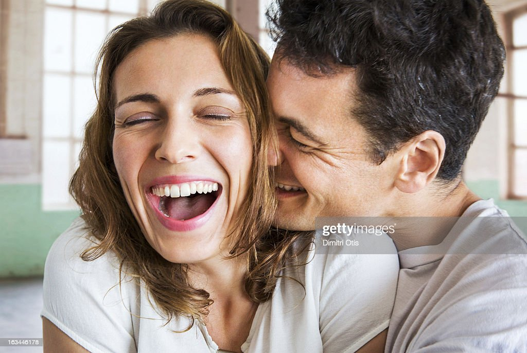 Romantic couple laughing and hugging intimately : Stock Photo