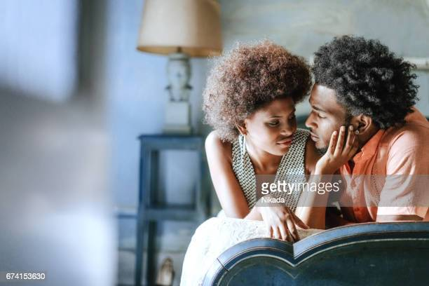romantic couple looking at each other while relaxing on bed at home - desire stock photos and pictures