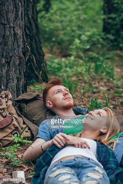 Romantic couple lying on field at forest