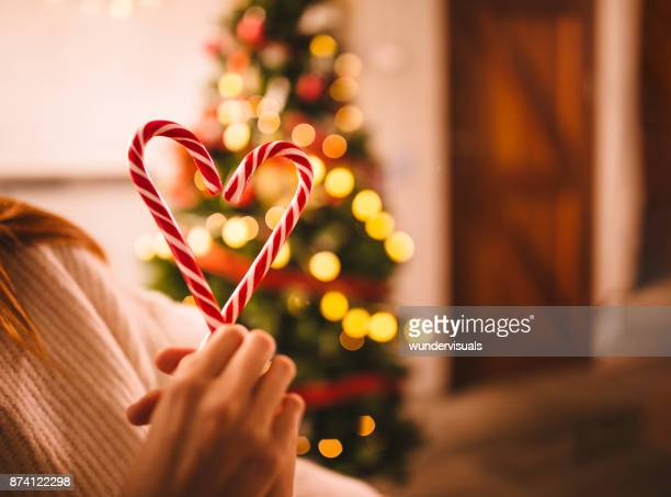 romantic couple making heart shape with christmas candy canes - candy cane stock pictures, royalty-free photos & images