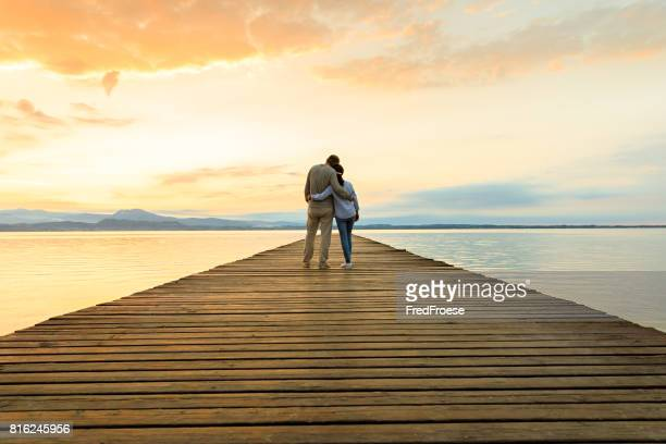 romantic couple on wooden jetty looking over the lake - amore foto e immagini stock
