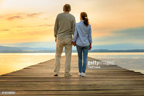 Romantic couple on wooden jetty looking over the lake