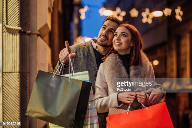 romantic couple pointing finger at shop item - high up stock pictures, royalty-free photos & images