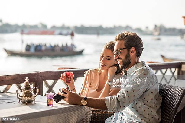 romantic couple reviewing camera at dubai marina cafe, united arab emirates - tradition stock pictures, royalty-free photos & images