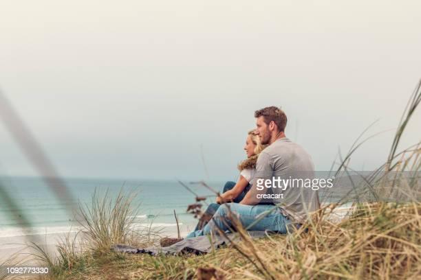 ロマンチックなカップルは、秋の日に砂丘フィストラル ビーチ、ニューキー コーンウォールの上に座っていた。 - イングランド コーンウォール ストックフォトと画像