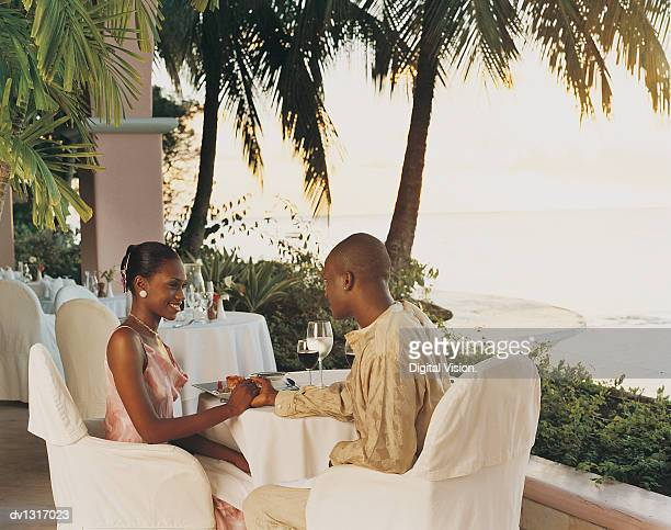 Romantic Couple Sitting in a Restaurant on the Coast Holding Hands