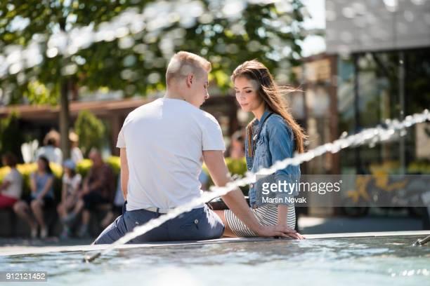 Romantic couple sitting near fountain