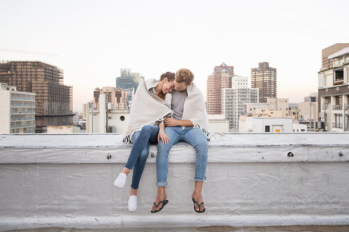 Romantic couple sitting on rooftop terrace, enjoying the view - gettyimageskorea