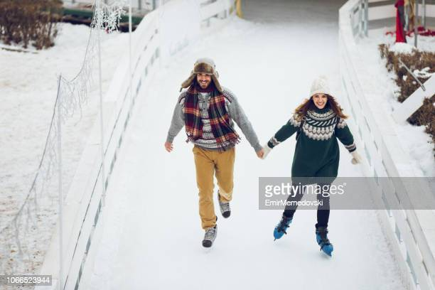 Romantic couple skating together in ice rink holding hands