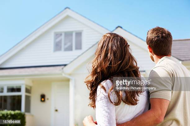 Romantic couple standing in front of their new house