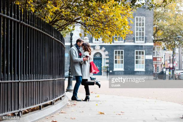 Romantic couple standing together by the city street.