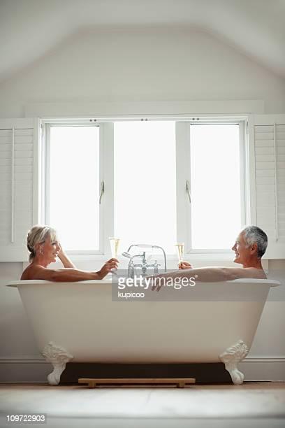 Romantic couple toasting champagne glasses in a bathtub