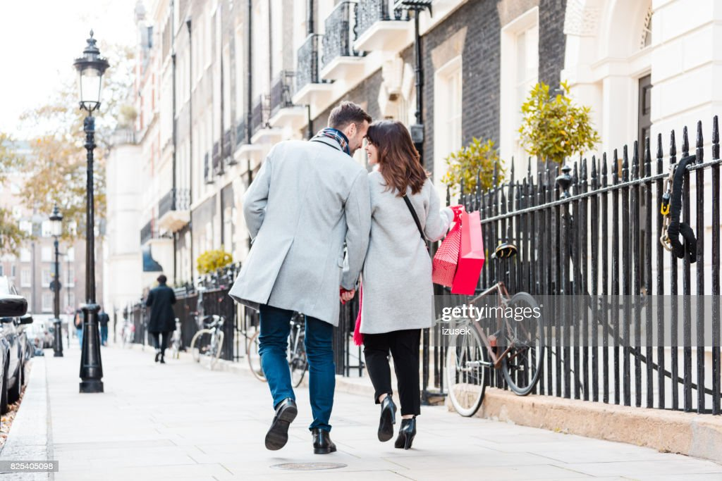 Romantic couple walking on the sidewalk : Stock Photo