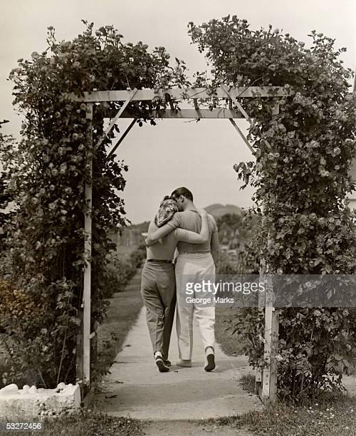 Romantic couple walking through rose arbor
