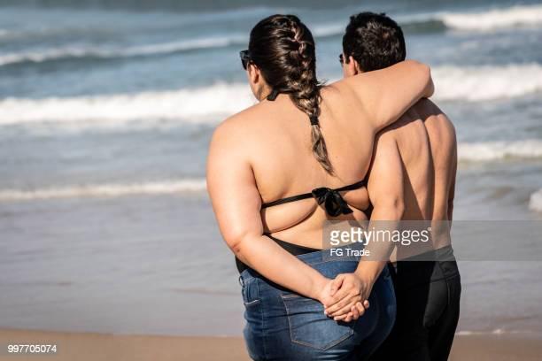 romántica pareja caminando juntos en la playa - modelos gorditas fotografías e imágenes de stock