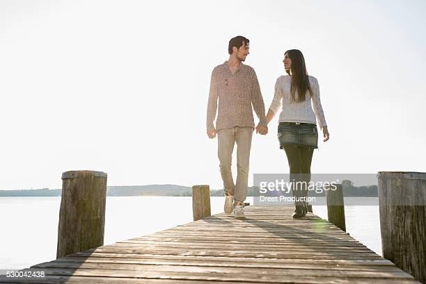 Romantic couple walking wooden jetty lake