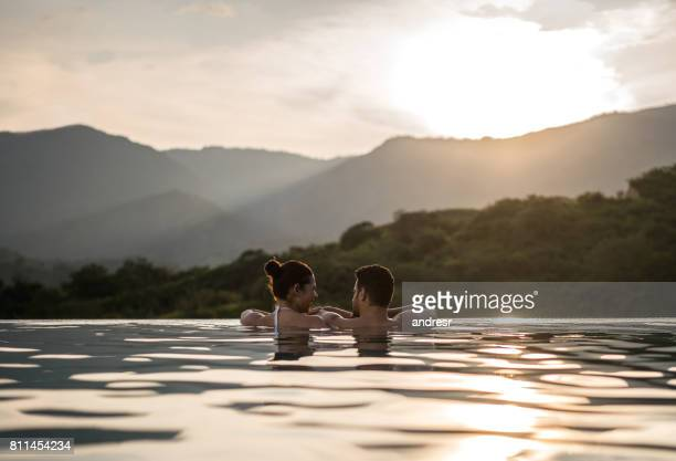 romantic couple watching the sunset in the swimming - honeymoon stock pictures, royalty-free photos & images