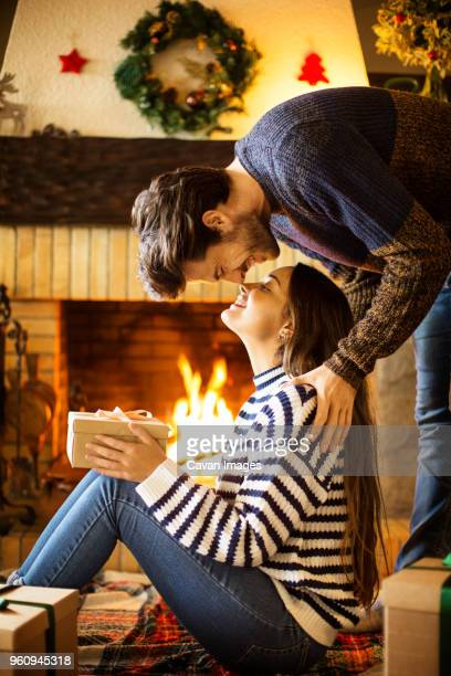 Romantic couple with Christmas present rubbing noses at home