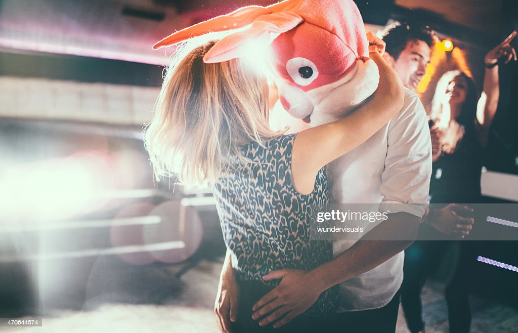 Romantic couple, with guy in a bunny head dancing together : Stock Photo