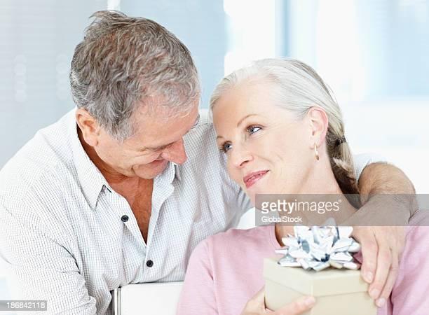 Romantique vieil homme donnant à son épouse un coffret cadeau
