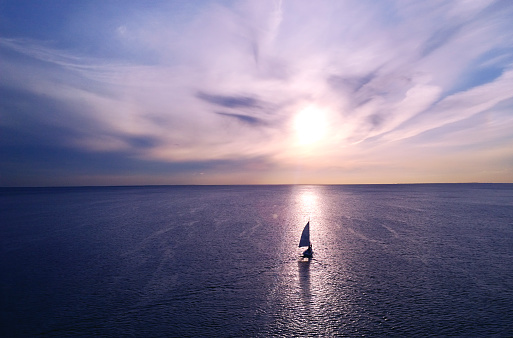 Romantic frame: yacht floating away into the distance towards the horizon in the rays of the setting sun. Purple-pink sunset 884343584