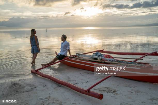 Romantic getaway in the Philippines Islands, couple enjoying sunset on the beach