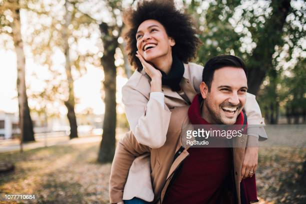 romantic happy couple piggyback riding in the park - valentines african american stock pictures, royalty-free photos & images