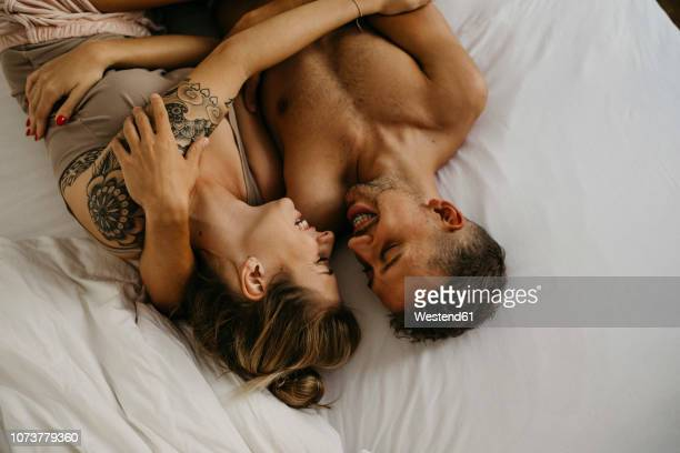 romantic happy young couple lying in bed - couple calin photos et images de collection