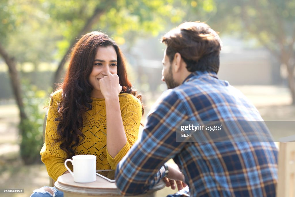 Romantic Indian couple having coffee at park : Stock Photo