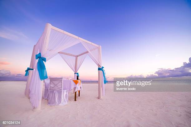 romantic luxury dinner setting at tropical beach on sunset - cadeira recostável - fotografias e filmes do acervo