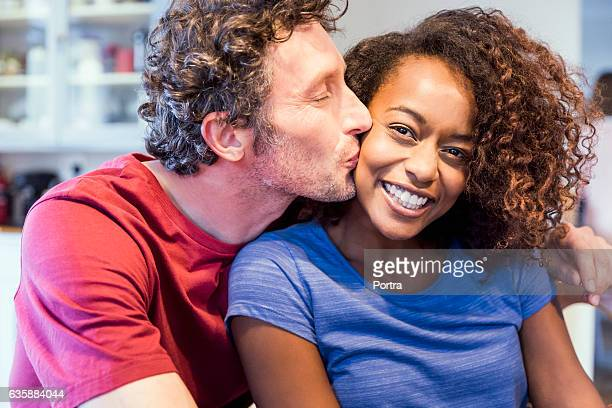 romantic man kissing cheerful woman on cheek - black people kissing stock pictures, royalty-free photos & images