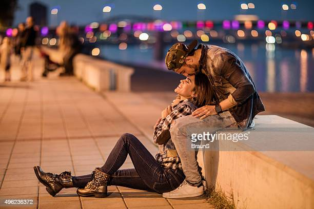 Romantic man kissing his girlfriend on a forehead at riverside.