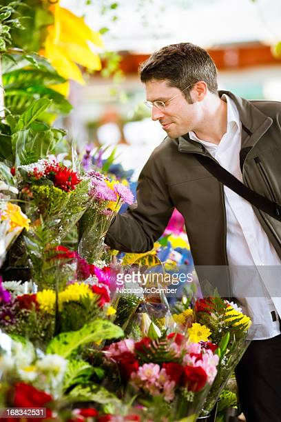 Romantic man shopping for flowers at market vertical