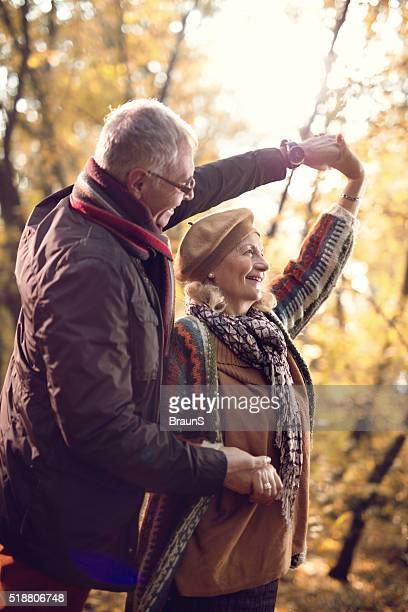 Romantic mature couple dancing while enjoying a day in nature.
