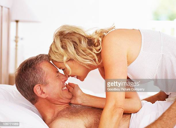 romantic mature couple in bed - older woman bending over stock pictures, royalty-free photos & images