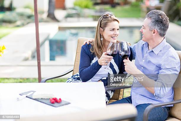 Romantic mature couple making a red wine toast at garden table