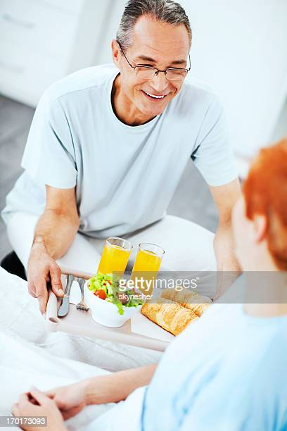 Romantic mature couple ready to have breakfast in bed