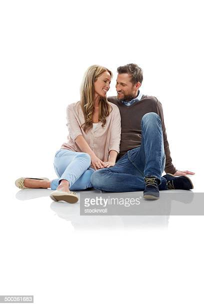 Romantic mature couple sitting over white