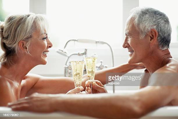 Romantic mature couple toasting with champagne in a bathtub