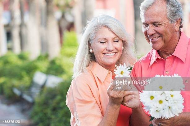 Romantic mature couple with bouquet of white daisies