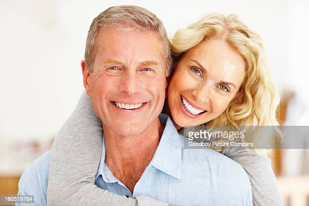 Romantic mature woman embracing man from behind