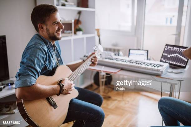 romantic musician playing acoustic guitar at home - producer stock pictures, royalty-free photos & images