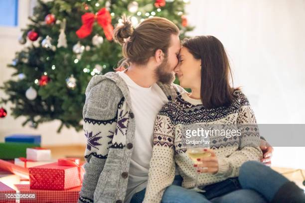 young heterosexual couple sitting carpet christmas