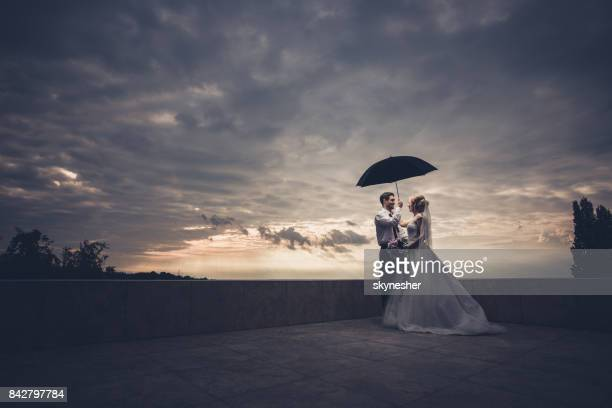 Romantic newlywed couple standing under umbrella on a terrace.