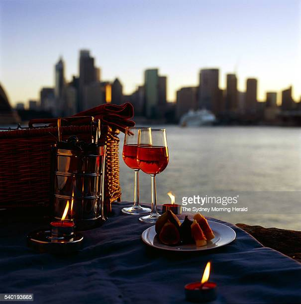 A romantic picnic basket full of wine figs cherries and other romantic goodies set with candles against a Sydney skyline on 12 February 2003 SMH...