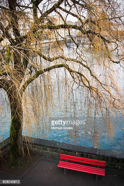 Romantic red park bench by river under weeping willow in Lucern Switzerland
