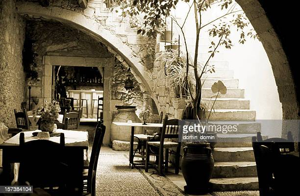 Romantic restaurant interior in Greece, wooden tables, chairs, sepia toned